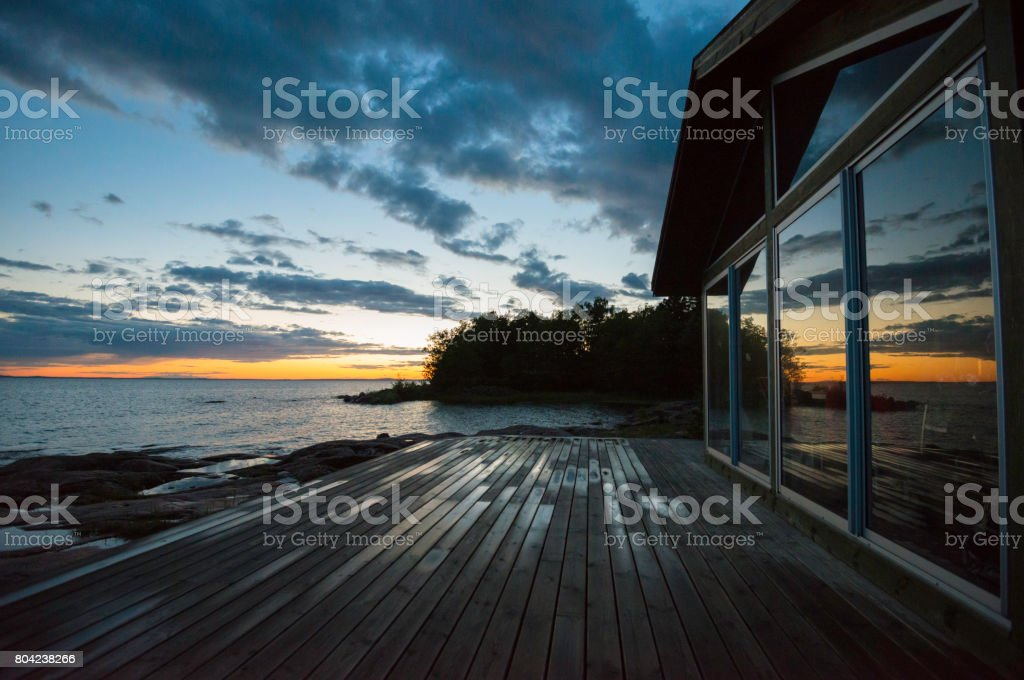 Sunset reflections on beach cottage after rain stock photo