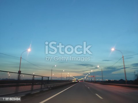 Sunset and sky, road running into the distance and evening lights
