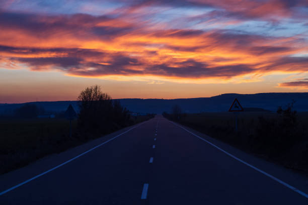 sunset road - carretera al atardecer - dotted line stock photos and pictures