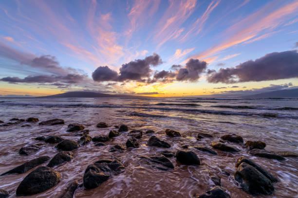 sunset rocky coast - une vue colorée de coucher du soleil à une rive rocheuse de la côte nord-ouest de l'île de maui, avec l'île de lanai à l'horizon. maui, hawaii, etats-unis. - paysage mois de mars photos et images de collection