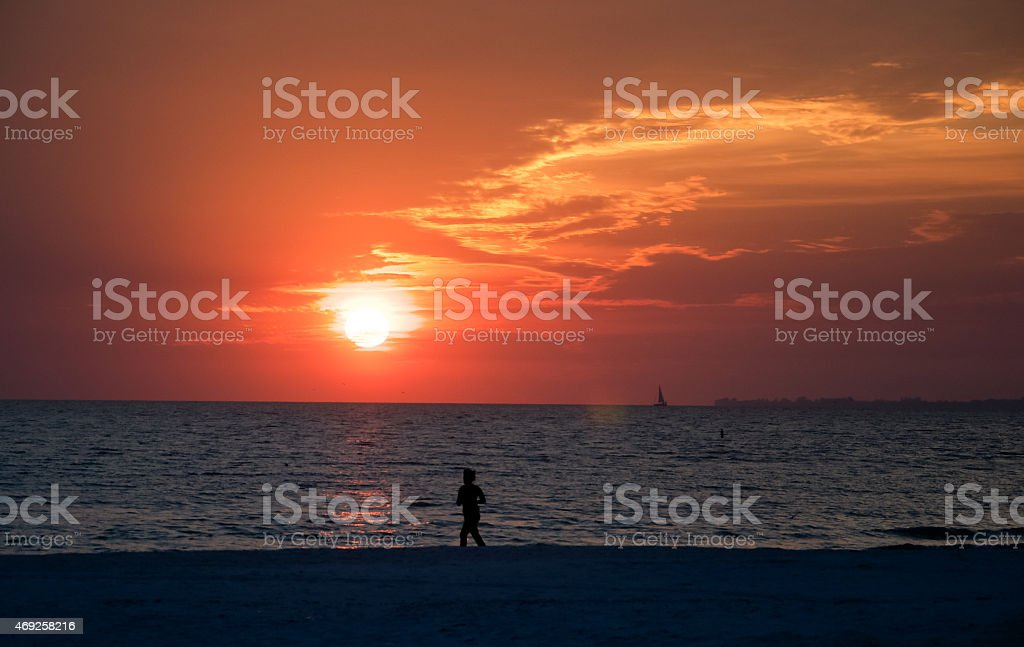 Sunset romance at the beach-a lonesome  jogger stock photo
