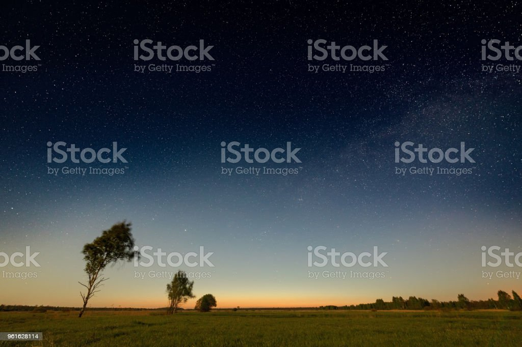 Sunset rural landscape with starry sky stock photo