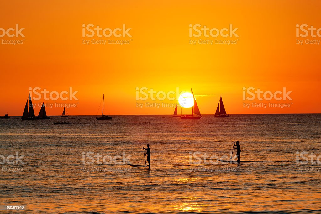 Sunset Sailing and Paddleboarding on Waikiki Beach of Honolulu Hawaii stock photo