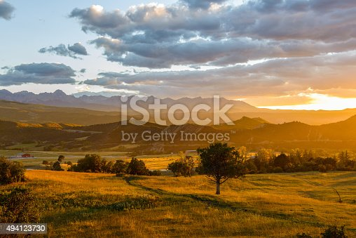 Autumn sunset scene of a mountain valley at foot of the rugged Sneffels Range, part of San Juan Mountains, in Colorado Rockies.
