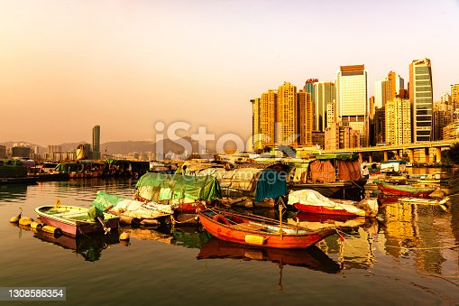 Sunset scene at the Causeway Bay Typhoon shelter in Victoria Harbour, Hong Kong with boats parked in the foreground and Kowloon side is seen at the background