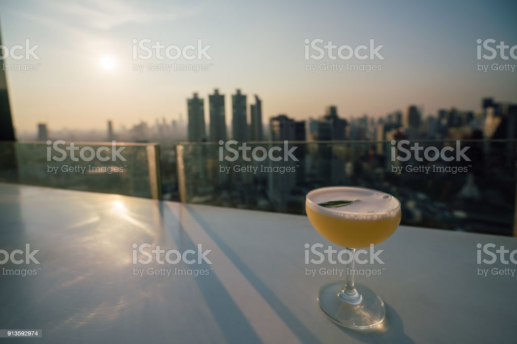 Sunset scene of cocktail put on table at rooftop sky bar in Bangkok city Thailand. - foto stock