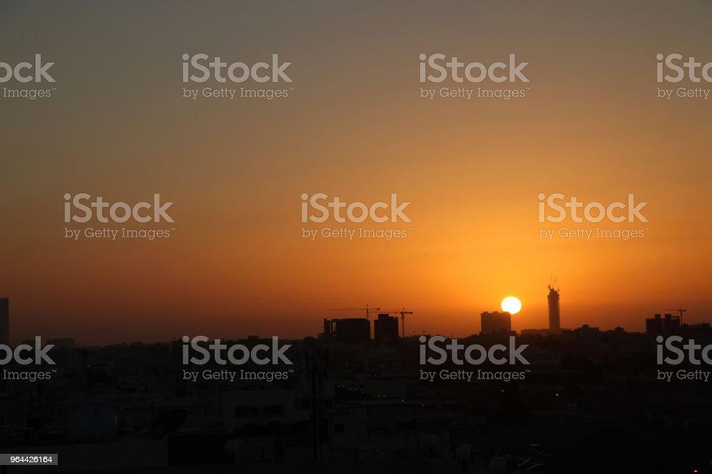 Cena do sol com a silhueta de edifícios na zona rural de Jeddah, Arábia Saudita - Foto de stock de Amarelo royalty-free