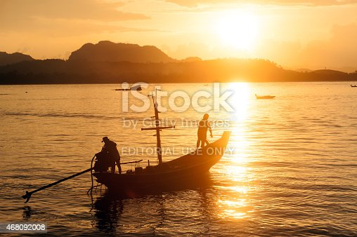 Chumphon,Thailand-April 6,2014 : Fisherman and his traditional fishing long tailed boat in the sea as the sunset.To return the Koh Phitak island on April 6,2014 at Chumphon Province,Southern of Thailand.