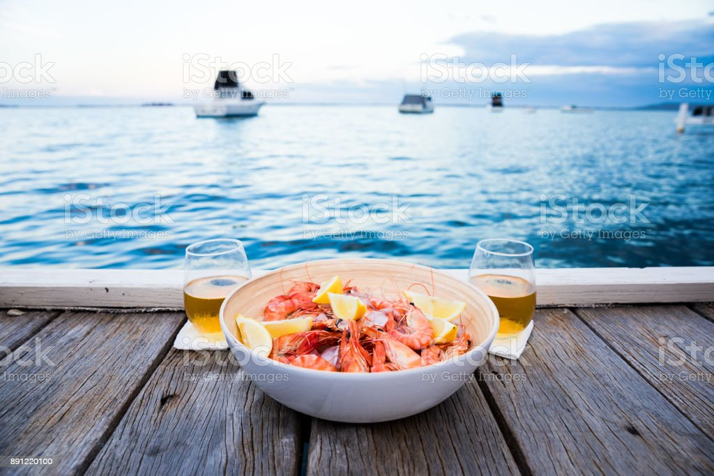 Sunset seafood snacks on jetty stock photo
