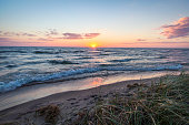 The sunset over the beautiful shores of Lake Michigan with dune grass in the foreground and sunset reflections on the sandy beach.