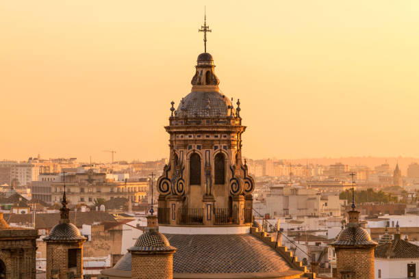 Sunset Seville - A close-up golden sunset view of the dome and bell tower at the top of the 16th-century Renaissance style Iglesia de la Anunciación - The Annunciation Church in Seville, Andalusia, Spain. stock photo