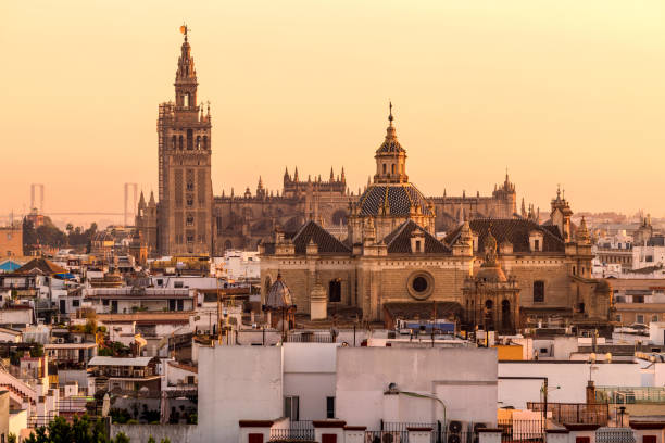 Sunset Seville - A panoramic golden sunset view of La Giralda tower and rooftop of Seville Cathedral rising behind soaring dome of the Church of the Divine Saviour. Seville, Andalusia, Spain. stock photo