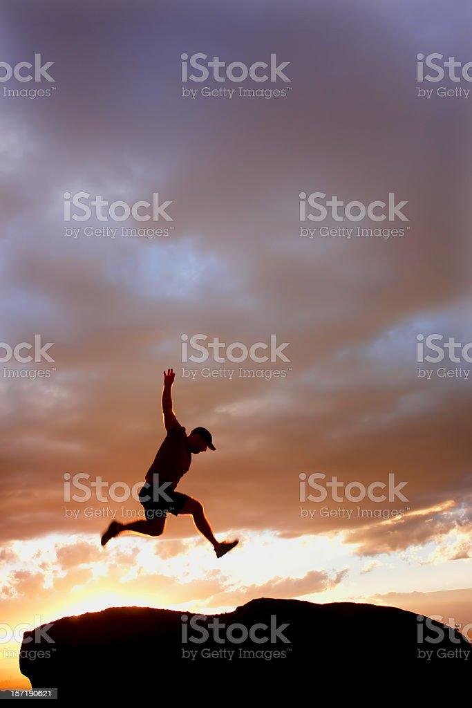 sunset silhouette man jumping stock photo