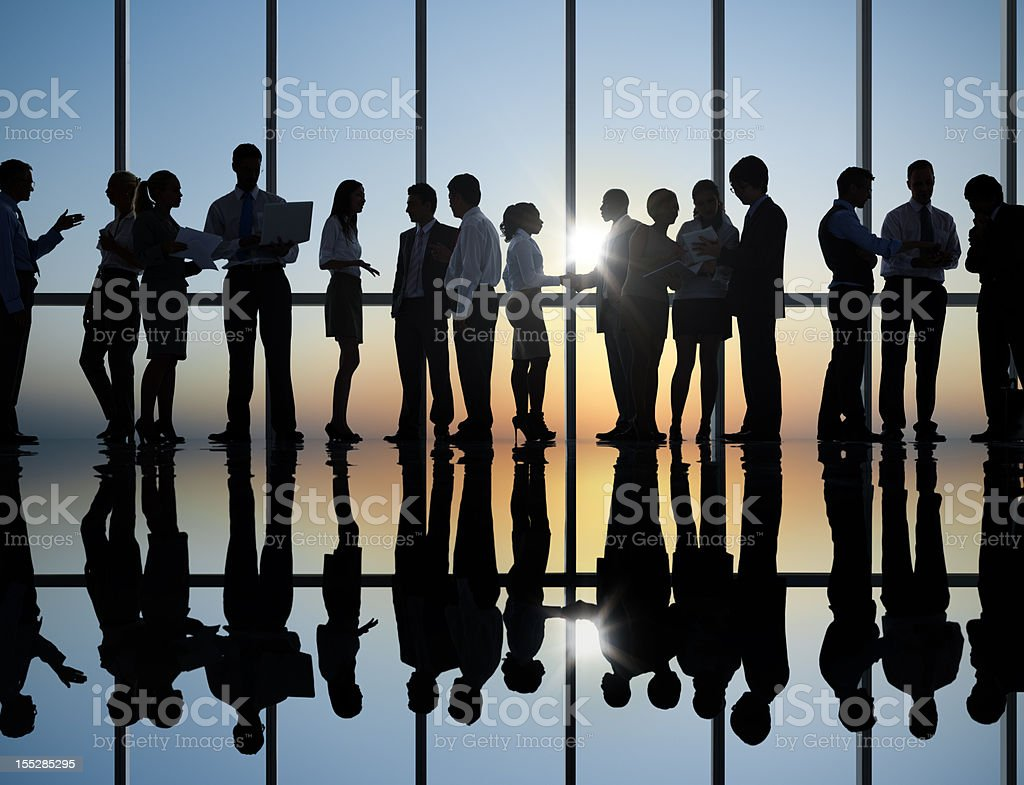 Sunset silhouette of business colleagues working royalty-free stock photo