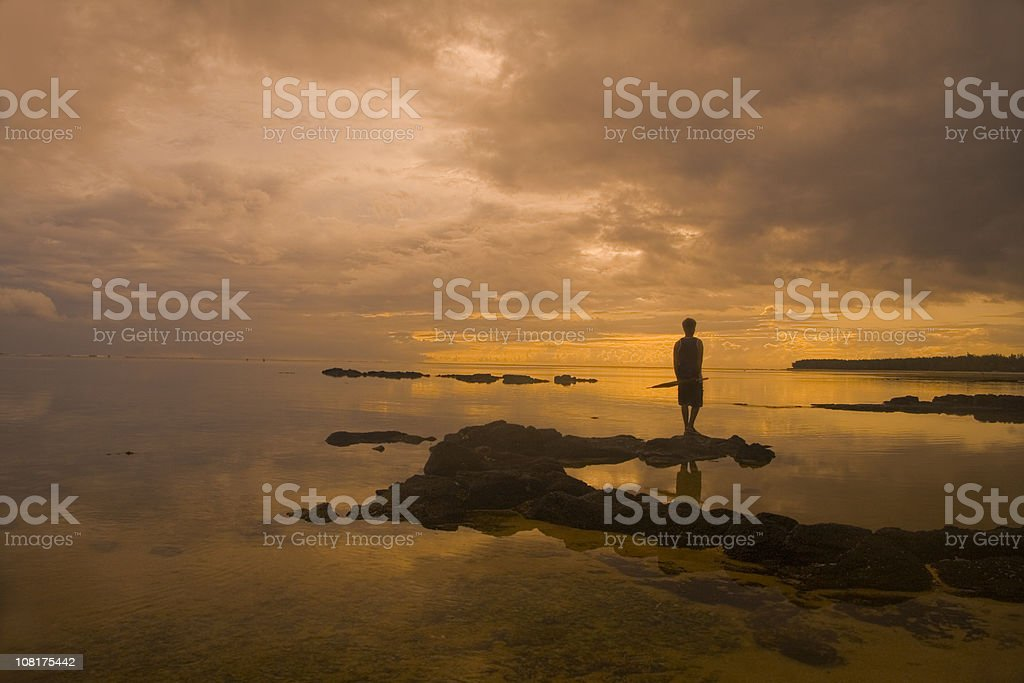 Sunset Silhouette of Man Standing on Rocks Near Calm Water royalty-free stock photo