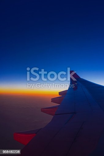 925925874 istock photo Sunset sky from the airplane window at height 35,000 feet. 958480208