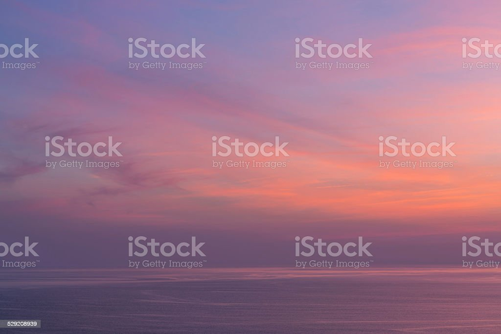 Sunset sky with clouds over the ocean stock photo