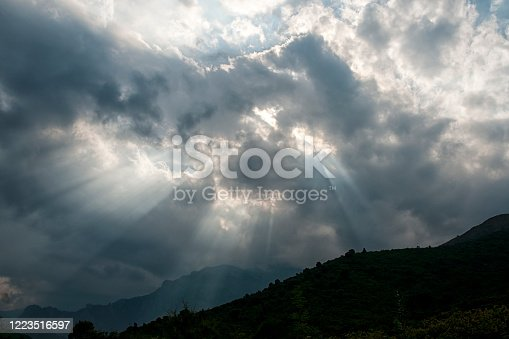 Sunset sky with ray of light, through the clouds