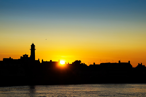 The sun setting over the rooftops at Gorleston-on-Sea in Norfolk, Eastern England, with buildings and the old lighthouse in silhouette. Gorleston-on-Sea is a town beside the River Yare, across the river from its larger neighbour Great Yarmouth.