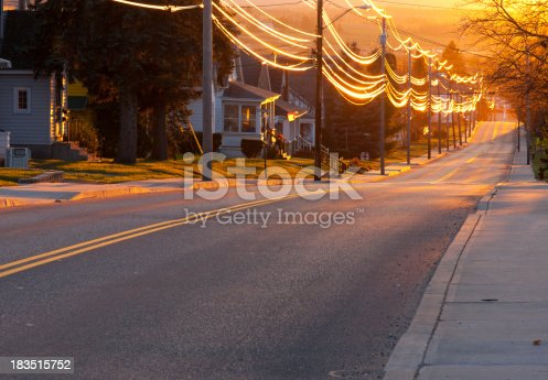 A view down a residential street at sunset.