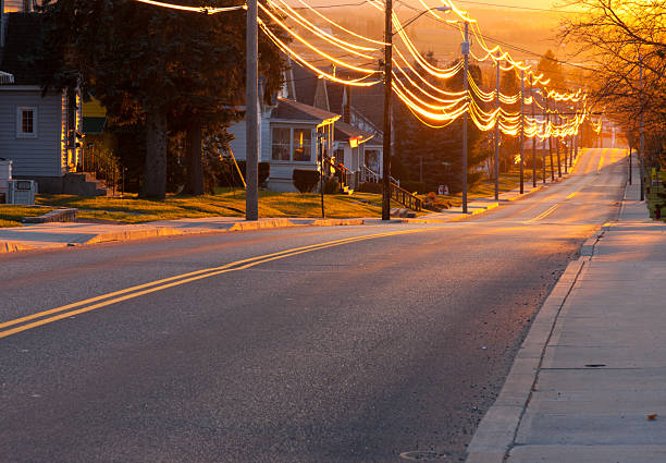 Sunset Street A view down a residential street at sunset. power line stock pictures, royalty-free photos & images