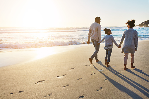 Shot of an adorable little girl going for a walk with her parents on the beach