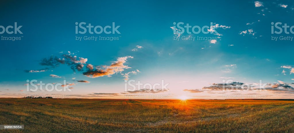 Sunset, Sunrise Rural Meadow Field In August Month. Countryside Landscape Under Scenic Summer Dramatic Sky In Sunset Dawn Sunrise. Sun Over Skyline Or Horizon. Panorama, Panoramic View stock photo