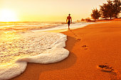 Photo of footprints in a sandy Hawaiian beach at sunset, leading to the silhouette of a surfer walking into the water with his surf board; Kauai, HI.