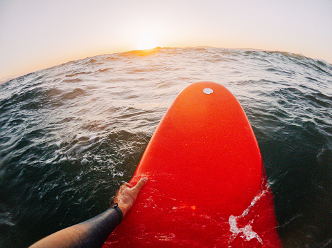 The first-person point of view of a surfer floating in the ocean while catching the waves on his surfboard.