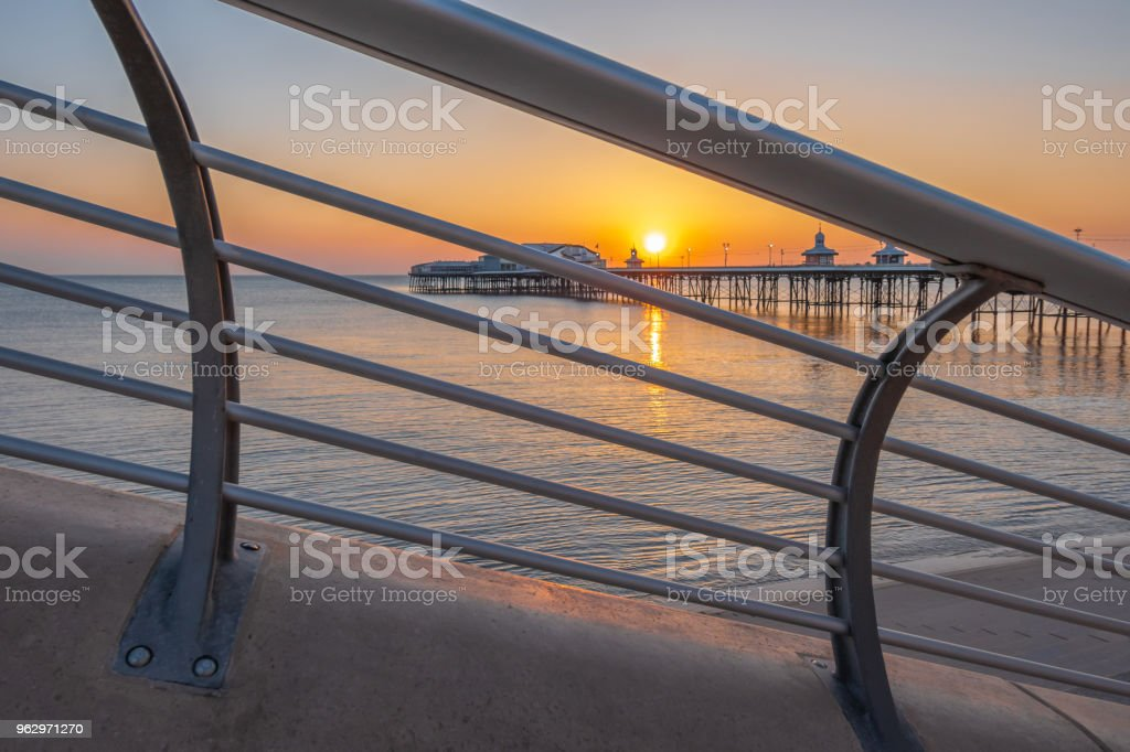 Sunset through a railing by the beach in Blackpool, Lancashire stock photo