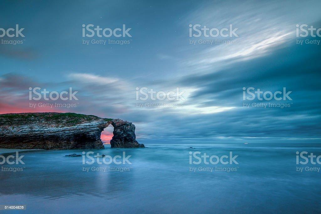 Sunset through the arch of As Catedrais beach stock photo