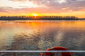 View of the sunset through the lifebuoy from the deck of the ship. Concept cruises and copy space