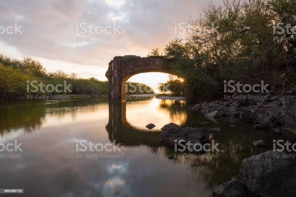 Sunset through the ruined bridge of Trois-Bassins in Reunion Island royalty-free stock photo