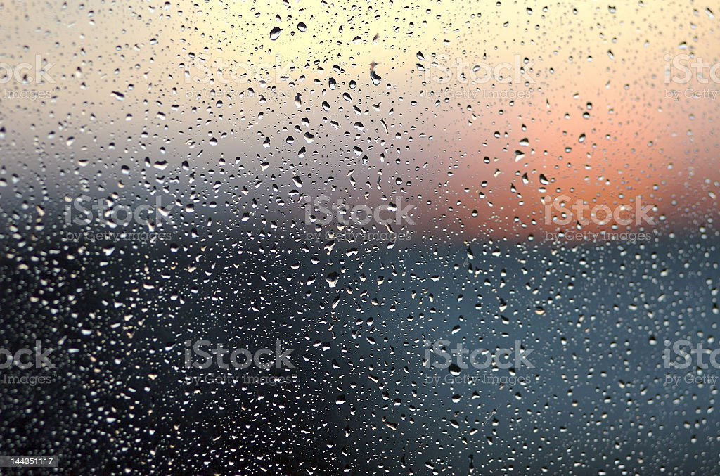 sunset through window with raindrops stock photo
