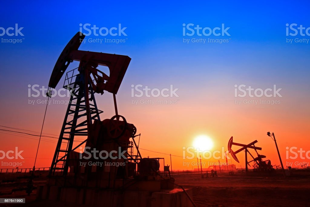 Sunset time of oil pump, oil industry equipment stock photo