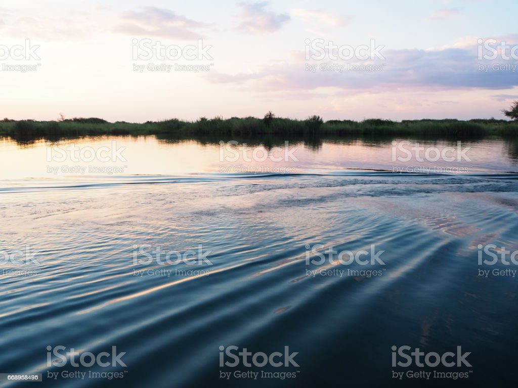 Sunset view at the river bank with water ripple and reflection foto stock royalty-free