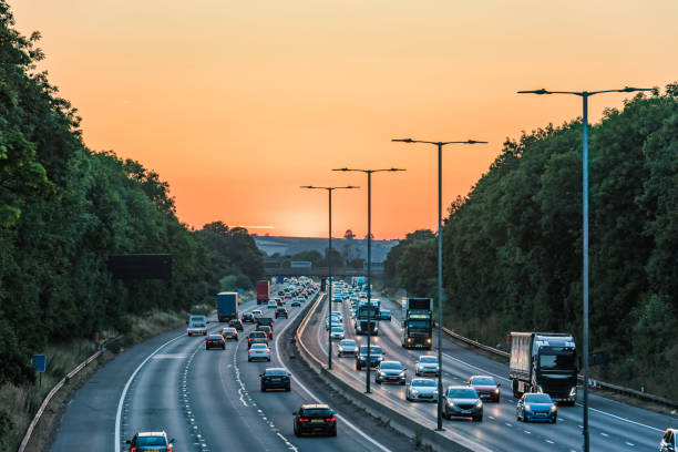 Sunset view of busy UK Motorway traffic in England Sunset view of busy UK Motorway traffic in England. multiple lane highway stock pictures, royalty-free photos & images