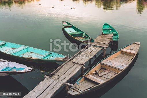 Beautiful golden sunset view of Dal lake at Srinagar, Jammu and Kashmir. Teal & orange wallpaper view with traditional Kashmiri Shikhara/boat. Serene scene of Kashmir. Boating, recreation, fun.