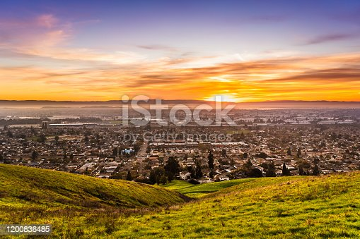 istock Sunset view of residential and industrial areas in East San Francisco Bay Area; green hills visible in the foreground; Hayward, California 1200836485