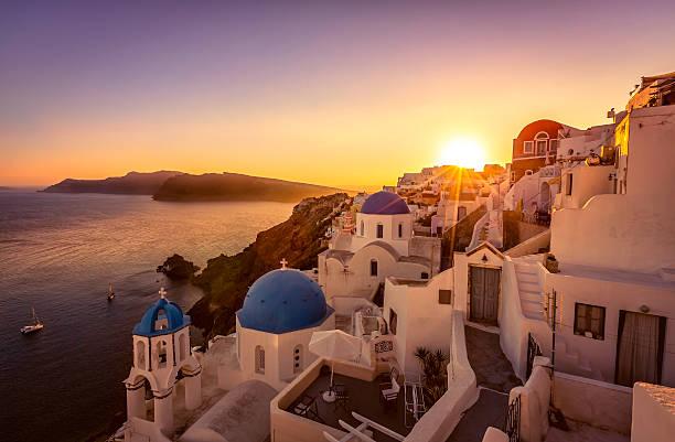 blick auf den sonnenuntergang von der blue-dome-kirchen von santorin, griechenland - fira stock-fotos und bilder