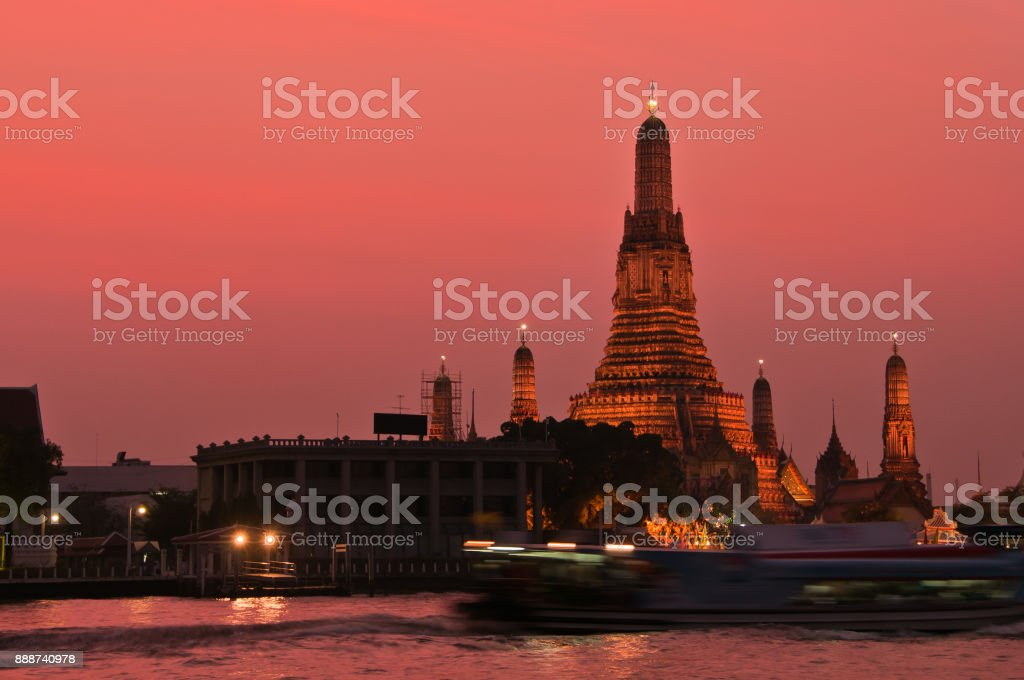 Sunset view of the main pagoda at Wat Arun from across the Chao Phraya River with speed boat passing by in front of the temple, at Bangkok, Thailand. stock photo