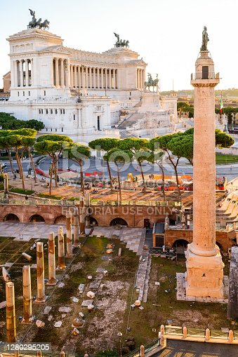 Rome, Italy, October 08 -- A sunset light view of the Trajan's Forum and column, the Altare della Patria or Vittoriano. The area of the Roman Imperial Forums is one of the most iconic of Rome, visited every year by thousands of residents and tourists, with the largest area of archaeological excavations in the world. The Vittoriano or Altare della Patria is the Italian national monument built between the Campidoglio (Roman Capitol Hill) and Piazza Venezia from 1885 and 1935 in honor of the first King of Italy, Vittorio Emanuele II. Inside there is the monument to the Unknown Soldier, the National Memorial dedicated to all Italian soldiers who died in wars. Image in High Definition format.