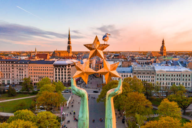 sunset view over Riga by the statue of liberty - Milda Beautiful sunset view over Riga by the statue of liberty - Milda in Latvia. The monument of freedom. People gathering around the monument for the concert. latvia stock pictures, royalty-free photos & images