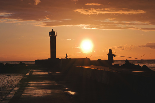 Sunset view with silhouette of senior woman fishing at baltic sea on Mangalsala pier in Riga