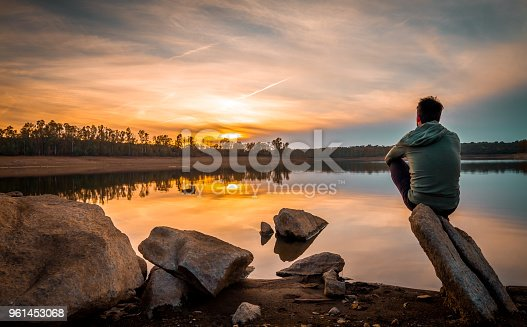 Portrait of his back in balance with the rock contemplating the sunset of the reservoir