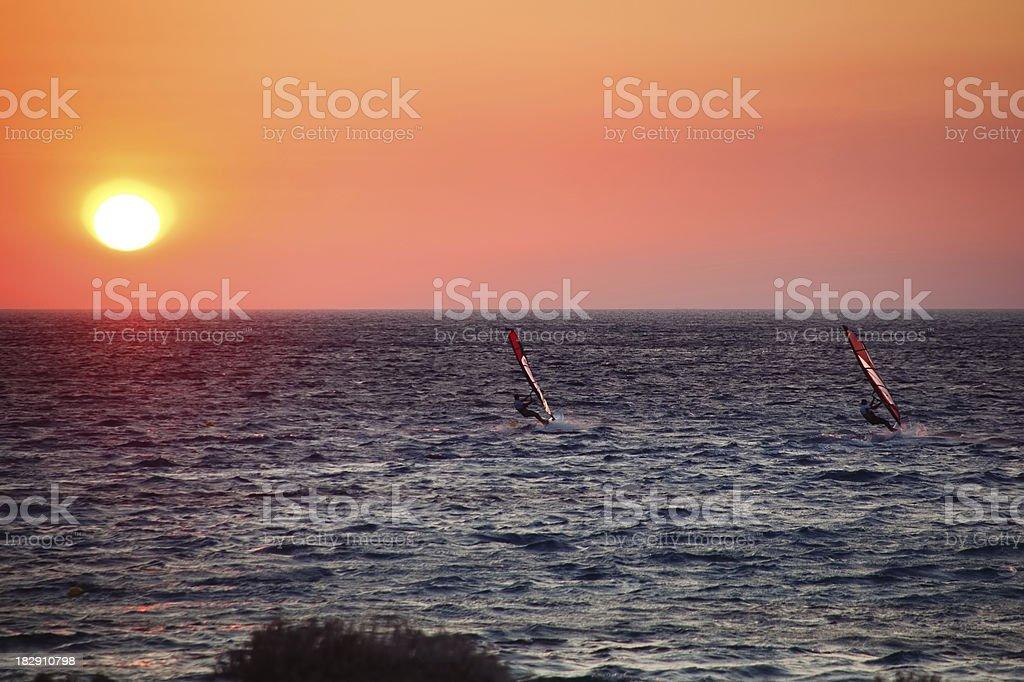 Sunset windsurfers stock photo