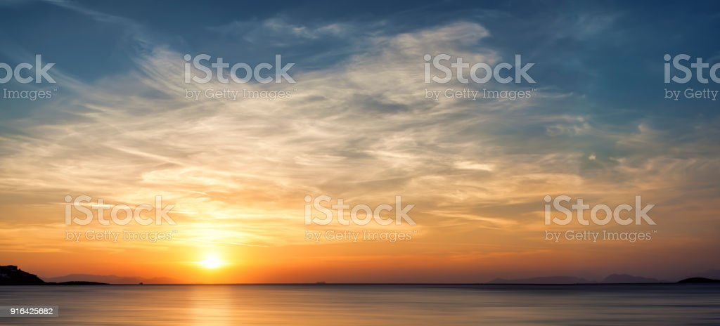 Sunset with clouds at the sea stock photo