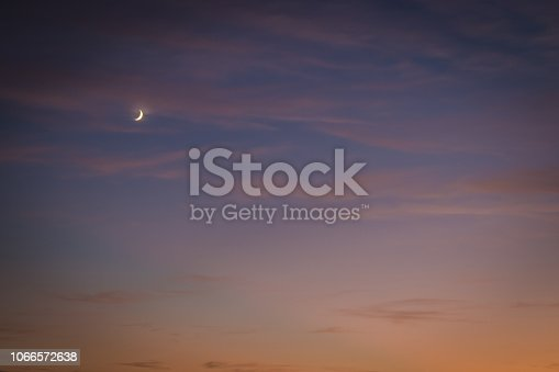 Dramatic sunset with moon with orange and purple sky