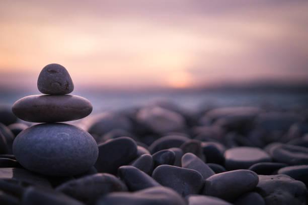 sonnenuntergang mit kieselsteinen am strand in nizza, frankreich. - gleichgewicht stock-fotos und bilder