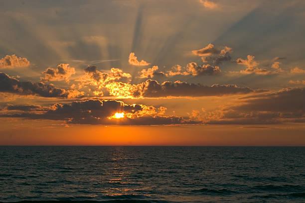 sonnenuntergang mit sonnenstrahlen of light - lake michigan strände stock-fotos und bilder
